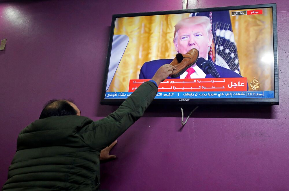 A Palestinian man places a shoe on a television screen broadcasting the announcement of Mideast peace plan by U.S. President Donald Trump, in a coffee shop in Hebron in the Israeli-occupied West Bank January 28, 2020.