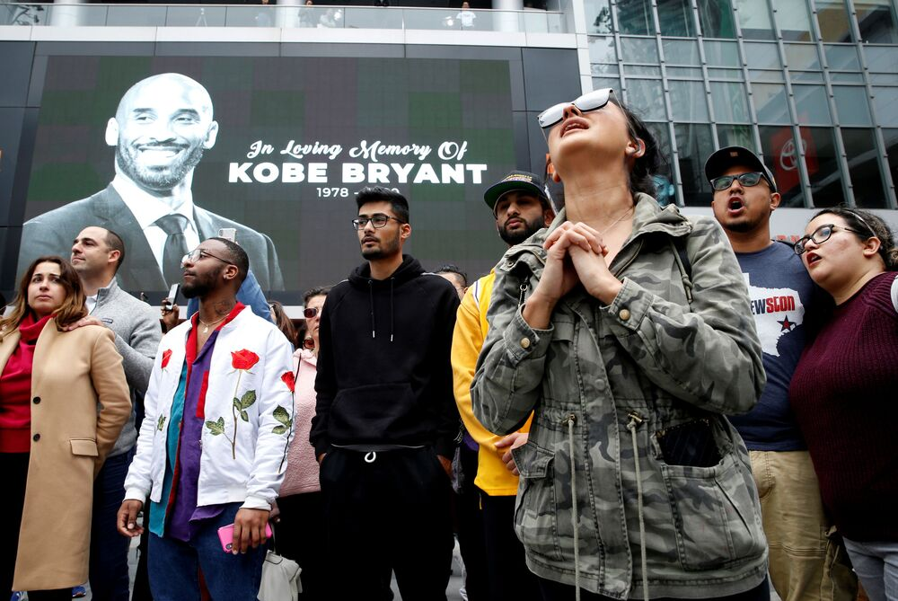 Mourners gather near an image of Kobe Bryant shown on a large screen outside the Staples Center after the retired Los Angeles Lakers basketball star was killed in a helicopter crash, in Los Angeles, California, U.S. January 26, 2020.