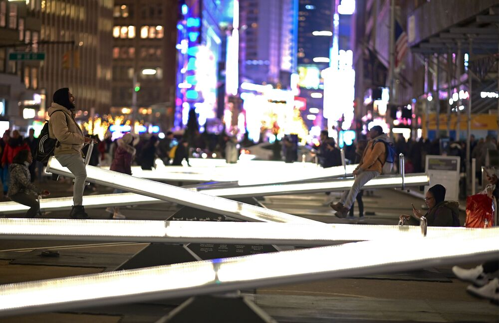 People play on an installation called Impulse,, twelve glowing seesaws, located on Broadway close to Time Square on January 29, 2020 in New York City.