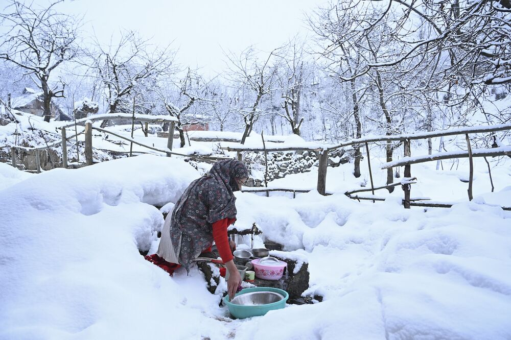 A woman washes utensils after a snowfall in the outskirts of Srinagar on January 29, 2020.