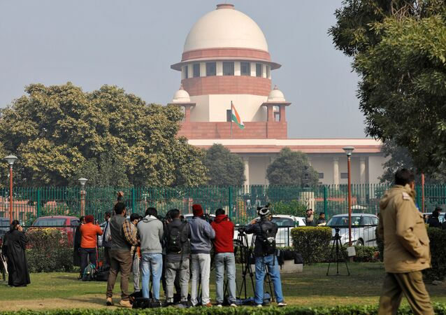 Television journalists are seen outside the premises of the Supreme Court in New Delhi, India, January 22, 2020.