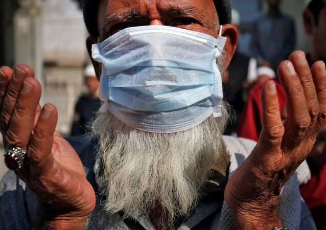 A Muslim wearing a mask prays for the victims of coronavirus at a mosque in Ahmedabad, India, January 31, 2020