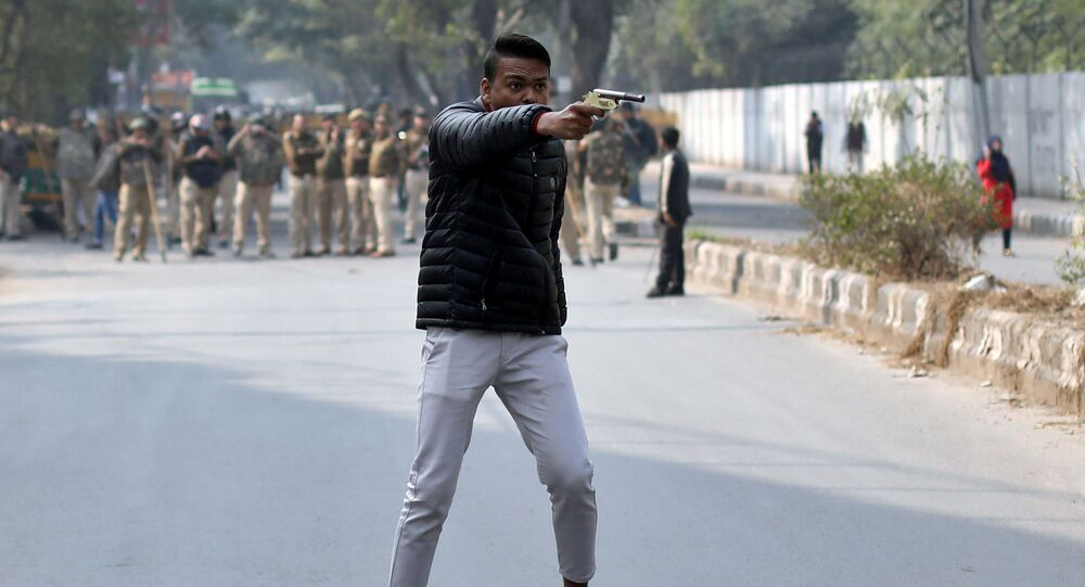 An unidentified man brandishes a gun during a protest against a new citizenship law outside the Jamia Millia Islamia university in New Delhi, India, January 30, 2020.