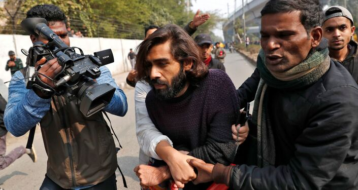 A wounded man is helped after an unidentified man opened fire during a protest against a new citizenship law outside the Jamia Millia Islamia university in New Delhi, India, January 30, 2020.