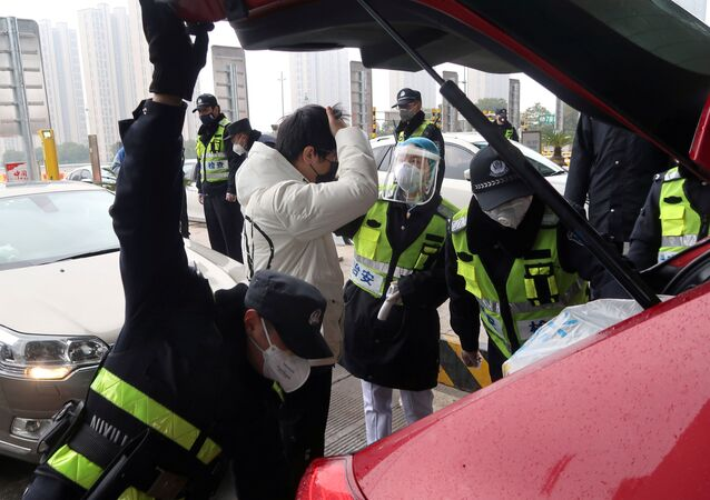 Police officers wearing masks check the boot of a car for smuggled wild animals following the outbreak of a new coronavirus, at an expressway toll station on the eve of the Chinese Lunar New Year celebrations, in Xianning, a city bordering Wuhan to the north, Hubei province, China January 24, 2020.