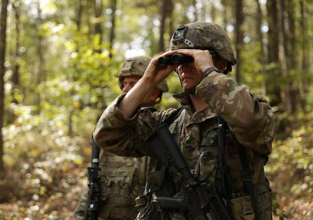U.S Army Sgt. Nicholas Wallace uses binoculars to scan the wooded area for possible threats during the 2019 HQDA Best Warrior Competition at Fort A.P. Hill, Virginia, Oct. 6, 2019
