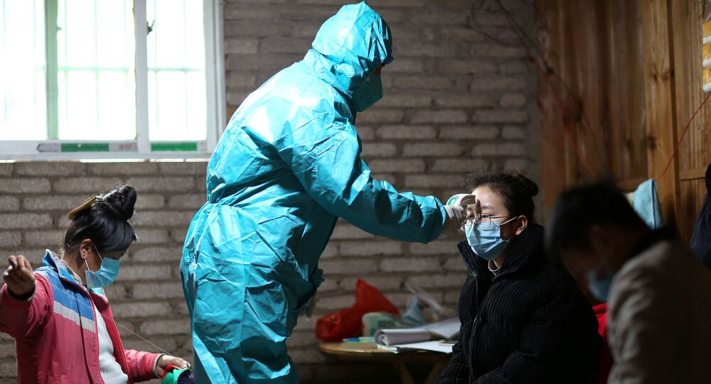 A medical worker in protective suit takes body temperature measurement of a villager as the country is hit by an outbreak of the new coronavirus, in Danzhai county, Qiandongnan Miao and Dong Autonomous Prefecture, Guizhou province, China January 31, 2020. Picture taken January 31, 2020.