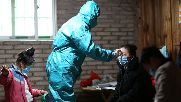 A medical worker in protective suit takes body temperature measurement of a villager as the country is hit by an outbreak of the new coronavirus, in Danzhai county, Qiandongnan Miao and Dong Autonomous Prefecture, Guizhou province, China January 31, 2020. Picture taken January 31, 2020. - Sputnik International