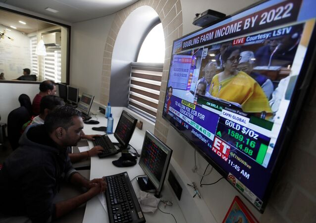 Brokers work at their computer terminal at a stock brokerage firm in Mumbai