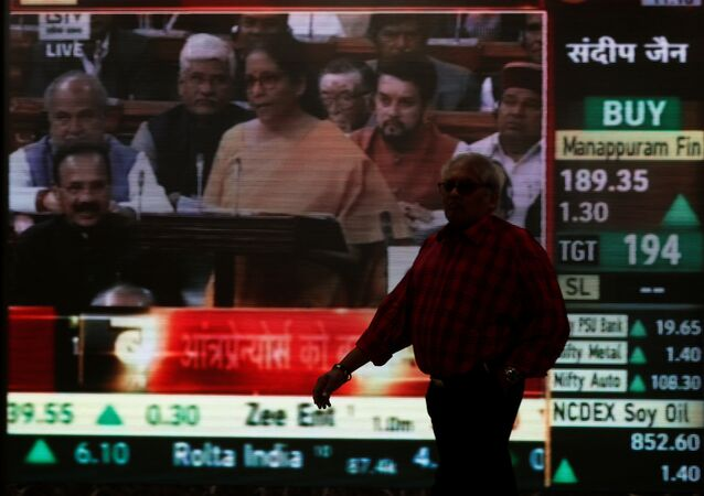 A man walks past a telecast of India's Finance Minister Nirmala Sitharaman presenting the budget inside the Bombay Stock Exchange