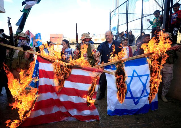 Demonstrators set fire to a makeshift Israeli and U.S. flag during a protest against U.S. President Donald Trump's Middle East peace plan, in Ain al-Hilweh Palestinian refugee camp, near Sidon, Lebanon January 29, 2020