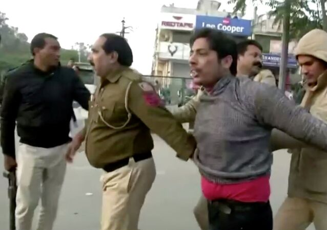 Police officers detain a man, who identified himself as Kapil Gujjar, who fired multiple shots at a site where people were protesting against a new citizenship law in New Delhi, India, February 1, 2020, in this still image taken from video