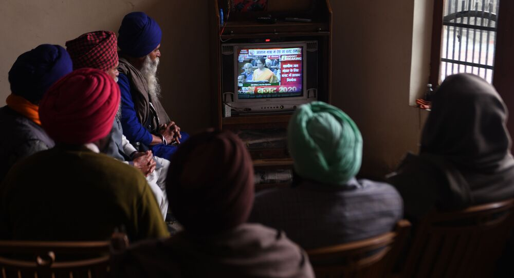 Farmers watch a news channel broadcasting India's Finance Minister Nirmala Sitharaman (C on screen) presenting the 2020 union budget, at a village on the outskirts of Amritsar on February 1, 2020.