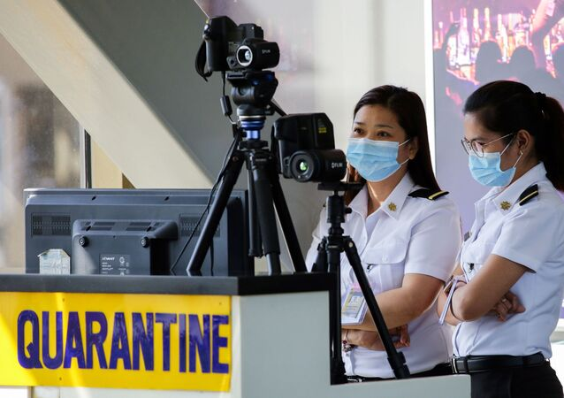 Airport personnel monitor a thermal scanner as passengers arrive at the Ninoy Aquino International Airport in Pasay, Philippines