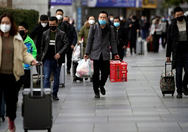 Passengers wearing masks walk outside the Shanghai railway station in Shanghai, China, as the country is hit by an outbreak of a new coronavirus, February 2, 2020