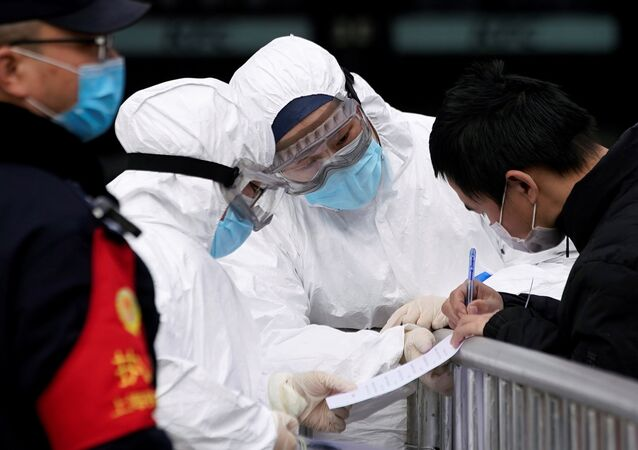 Staff members wearing protective masks check a passenger at Shanghai railway station in Shanghai, China, as the country is hit by an outbreak of a new coronavirus, February 2, 2020.
