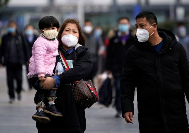 Passengers wearing masks walk outside the Shanghai railway station in Shanghai, China, as the country is hit by an outbreak of a new coronavirus, February 2, 2020.