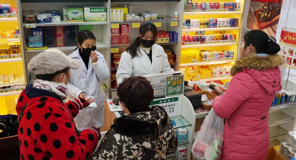 Staff sell masks at a Yifeng Pharmacy in Wuhan, Chin