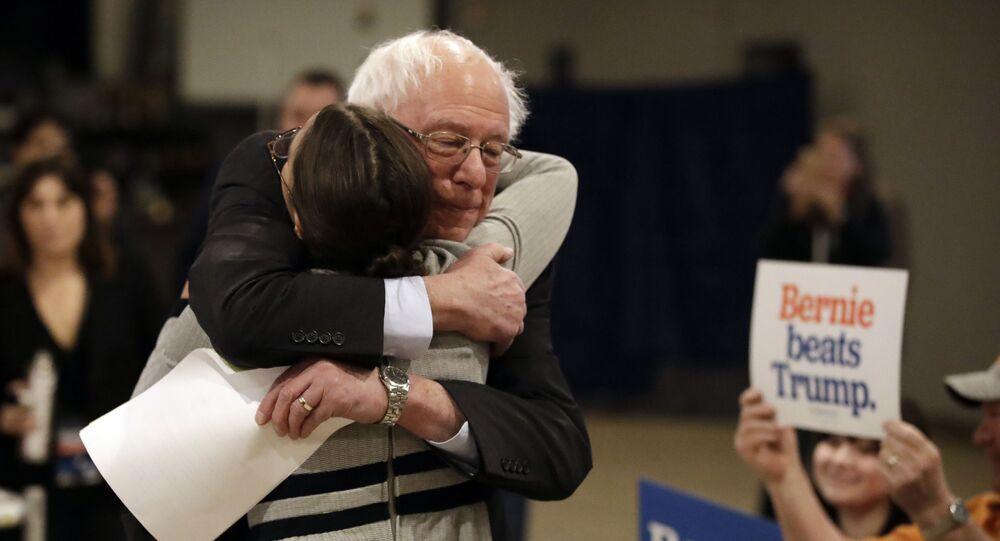 Democratic presidential candidate Sen. Bernie Sanders, I-Vt., center, hugs Rep. Alexandria Ocasio-Cortez, D-N.Y.