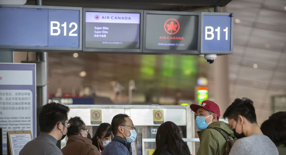 Travelers wearing face masks at the Air Canada check-in counters at Beijing Capital International Airport in Beijing