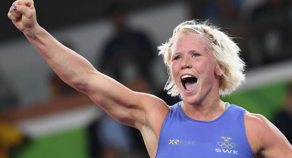 Sweden's Anna Jenny Fransson (blue) celebrates after winning against Canada's Dorothy Erzsebet Yeats in their women's 69kg freestyle bronze medal match on August 17, 2016, during the wrestling event of the Rio 2016 Olympic Games at the Carioca Arena 2 in Rio de Janeiro