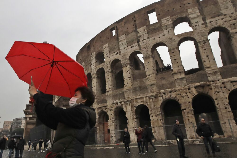 A tourist wearing a mask takes a selfie in front of Rome's ancient Colosseum, Saturday, 1 Feb. 2020. Italy banned all flights coming from and going to China as European countries have stepped up their response to the new virus that has sickened thousands of people in China and reached 19 other countries. Italy has reported two cases.