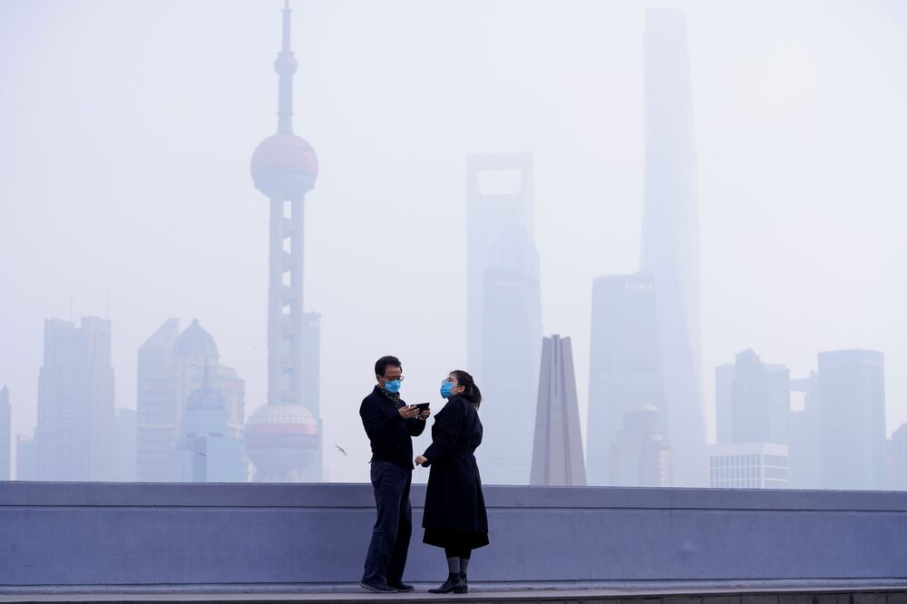 People wearing masks are seen on a bridge in front of the financial district of Pudong in Shanghai, China, as the country is hit by an outbreak of a new coronavirus, 3 February 2020.