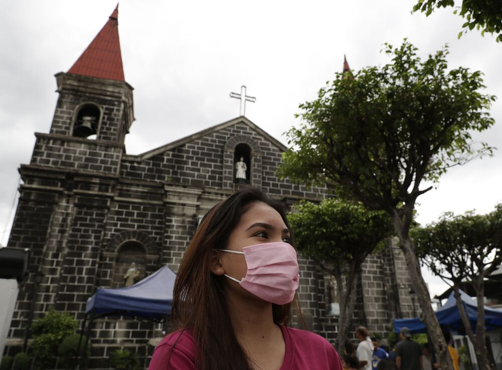 A woman wearing a protective mask walks outside a church in Mandaluyong, east of Manila, Philippines on Sunday, 2 Feb. 2020. The Philippines on Sunday reported the first death of the new virus outside of China, where authorities delayed the opening of schools in the worst-hit province and tightened quarantine measures in another that allow only one family member to venture out to buy supplies.