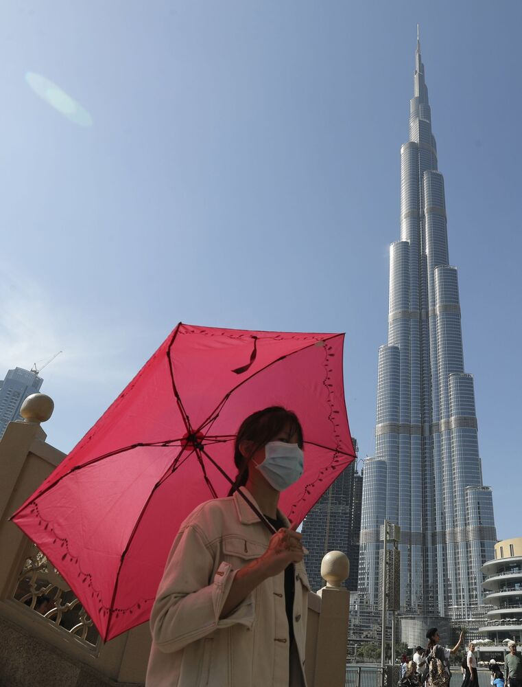 In this Thursday, 30 Jan. 2020 photo, a Chinese woman wearing a protective face mask walks beneath the world's tallest tower, the Burj Khalifa, in Dubai, the United Arab Emirates. The World Health Organisation declared the outbreak sparked by a new virus in China that has been exported to more than a dozen countries a global emergency on Thursday after the number of cases spiked tenfold in a week.