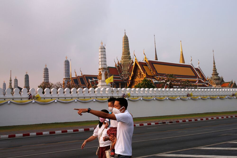 A family wears masks to prevent the spread of the new coronavirus as they walk near the Grand Palace at Bangkok, Thailand, 2 February 2020. REUTERS