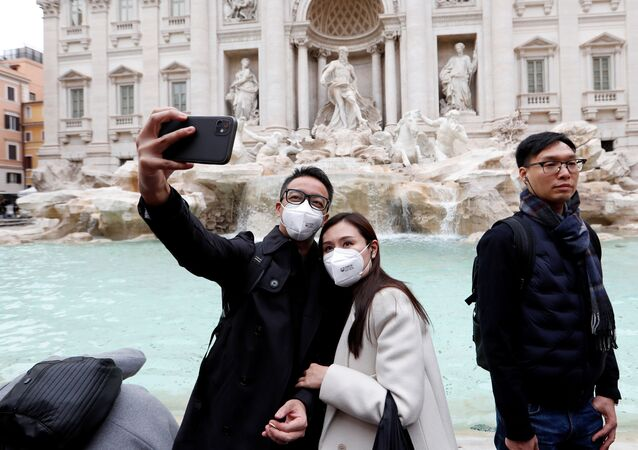Tourists wearing protective masks take a selfie in front of the Trevi's Fountain after two cases of coronavirus were confirmed in the country, in Rome, Italy