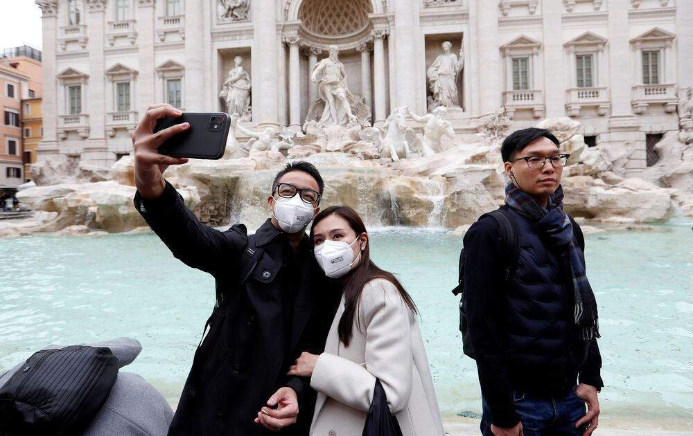 Tourists wearing protective masks take a selfie in front of the Trevi's Fountain after two cases of coronavirus were confirmed in in the country, in Rome, Italy, 31January 2020.