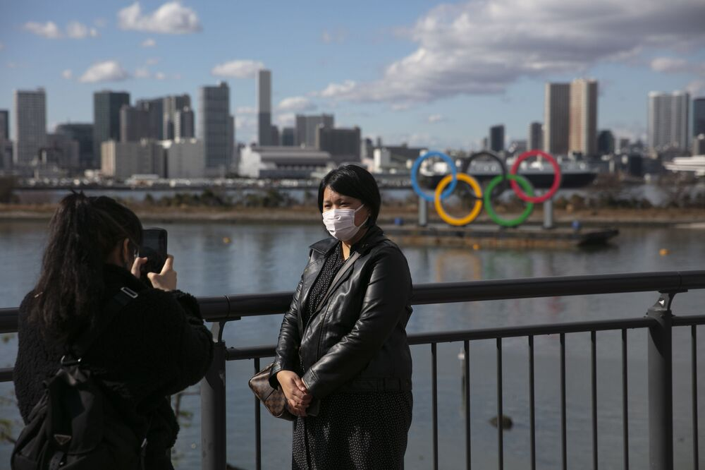 A tourist wearing a mask pauses for photos with the Olympic rings in the background Wednesday, 29 Jan. 2020, in the Odaiba district of Tokyo. Japanese officials say four evacuees on a flight from the Chinese city of Wuhan have a cough and fever. The Tokyo Metropolitan Government confirmed their condition after the flight of 206 evacuees arrived in the city.