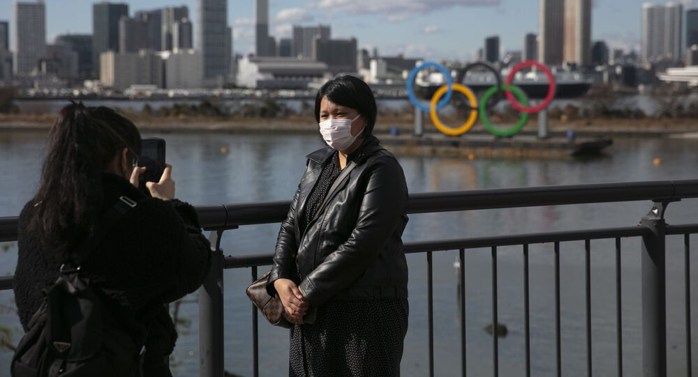 A tourist wearing a mask pauses for photos with the Olympic rings