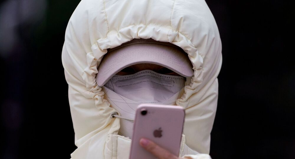 A woman wearing a mask checks her mobile phone in Shanghai, China January 29, 2020