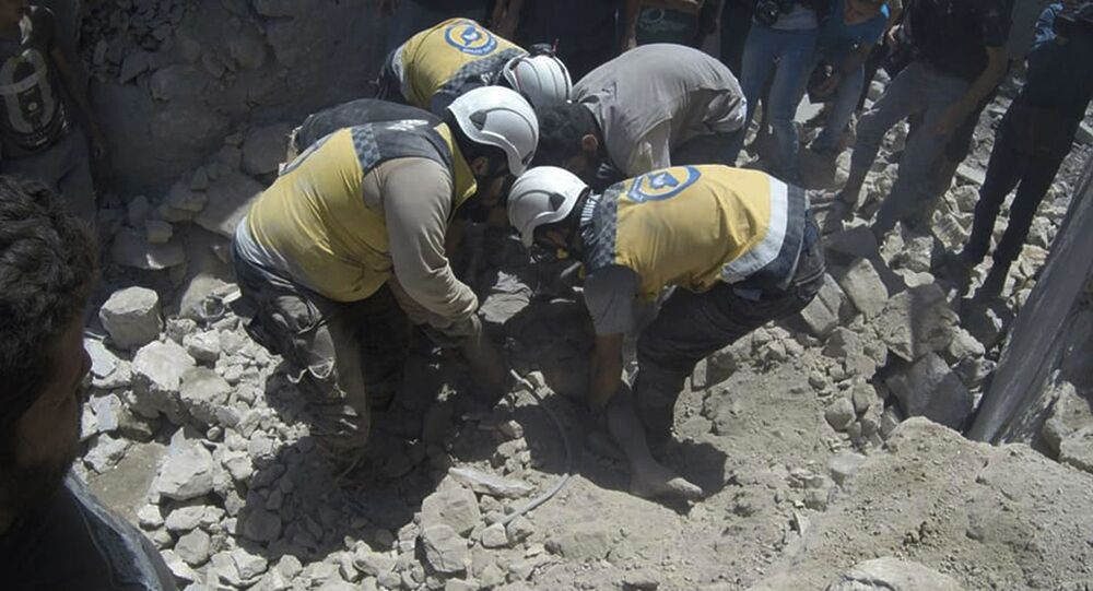 This photo provided by the Syrian Civil Defense White Helmets, which has been authenticated based on its contents and other AP reporting, shows Syrian White Helmet civil defense workers pull out a victim from under the rubble of a destroyed building that hit by a Syrian government airstrike, in the northern town of Ariha, in Idlib province, Syria, Friday, July 12, 2019
