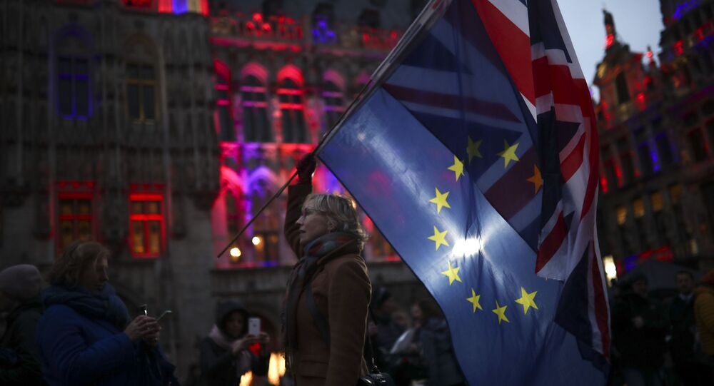 A woman holds up the Union and the European Union flags during an event called Brussels calling to celebrate the friendship between Belgium and Britain at the Grand Place in Brussels, Thursday, Jan. 30, 2020