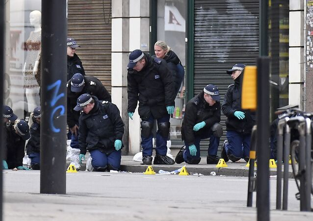 Police officers work at the scene of Sunday's terror stabbing attack in the Streatham area of south London