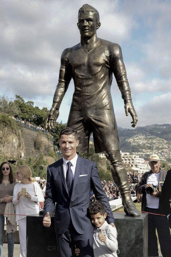 Cristiano Ronaldo with his son under a statue of himself during the opening ceremony in his hometown of Funchal, 2014.