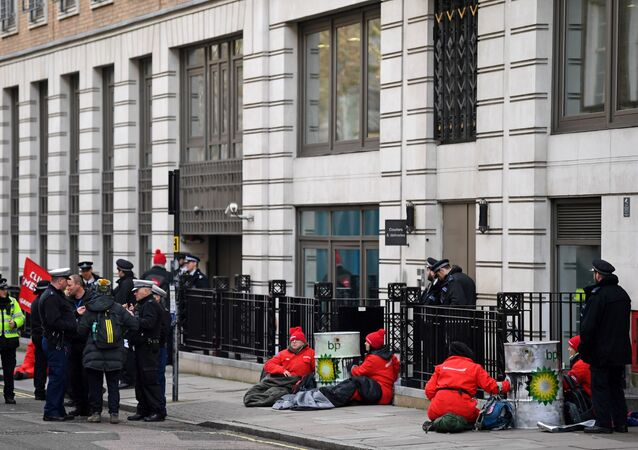 Greenpeace activists sit chained into oil barrels as they protest outside the headquarters of oil giant BP in London on February 5, 2020, on the day that the company's new CEO, Bernard Looney was set to take up his role