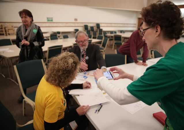 A precinct worker documents the process with her phone as Iowa Caucus precinct workers count  paper ballots after a Democratic presidential caucus at West Des Moines Christian Church in West Des Moines, Iowa, U.S., February 3, 2020