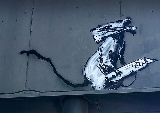An artwork depicting a masked rat by British street-artist Banksy on the back of a parking sign in Paris