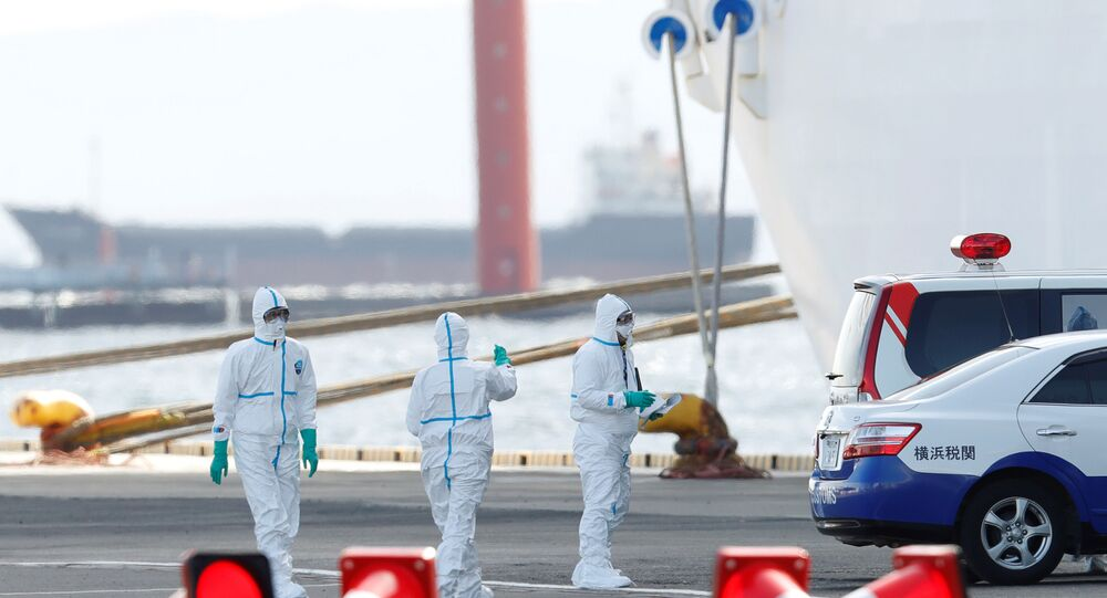 Workers wearing protective gear at Daikoku Pier Cruise Terminal in Yokohama, south of Tokyo, Japan