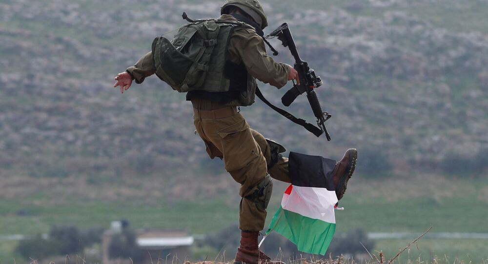 An Israeli soldier kicks a Palestinian flag during a protest against the US President Donald Trump's Middle East peace plan in the Jordan Valley in the Israeli-occupied West Bank 29 January 2020