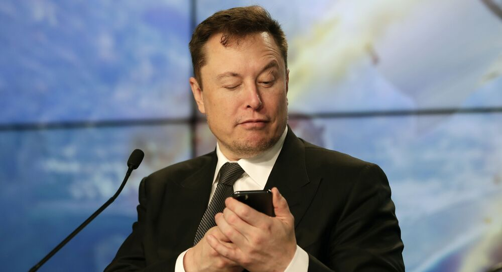 Elon Musk founder, CEO, and chief engineer/designer of SpaceX jokes with reporters as he pretends to be searching for an answer to a question on a cell phone during a news conference after a Falcon 9 SpaceX rocket test flight to demonstrate the capsule's emergency escape system at the Kennedy Space Center in Cape Canaveral, Fla., Sunday, Jan. 19, 2020.