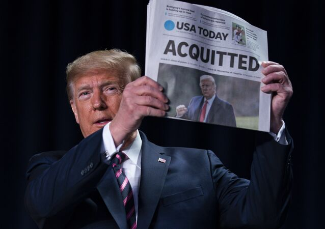 President Donald Trump holds up a newspaper with the headline that reads ACQUITTED at the 68th annual National Prayer Breakfast, at the Washington Hilton, Thursday, Feb. 6, 2020, in Washington.