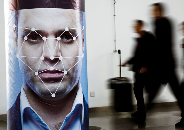 People walk past a poster simulating facial recognition software at the Security China 2018 exhibition on public safety and security in Beijing, China October 24, 2018
