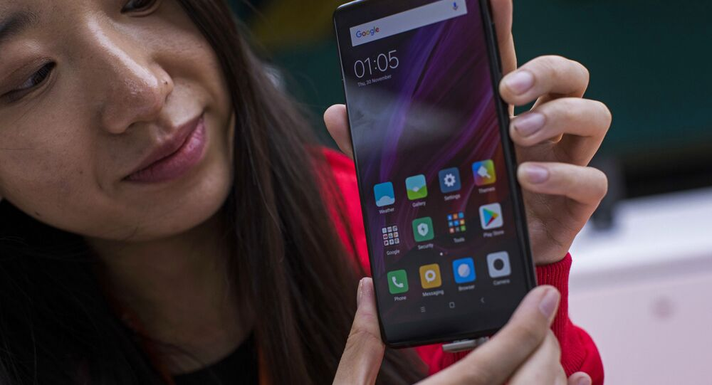 In this Feb. 26, 2018 file photo, a woman shows the new Xiaomi Mi MIX 2 during the Mobile World Congress wireless show, in Barcelona, Spain.