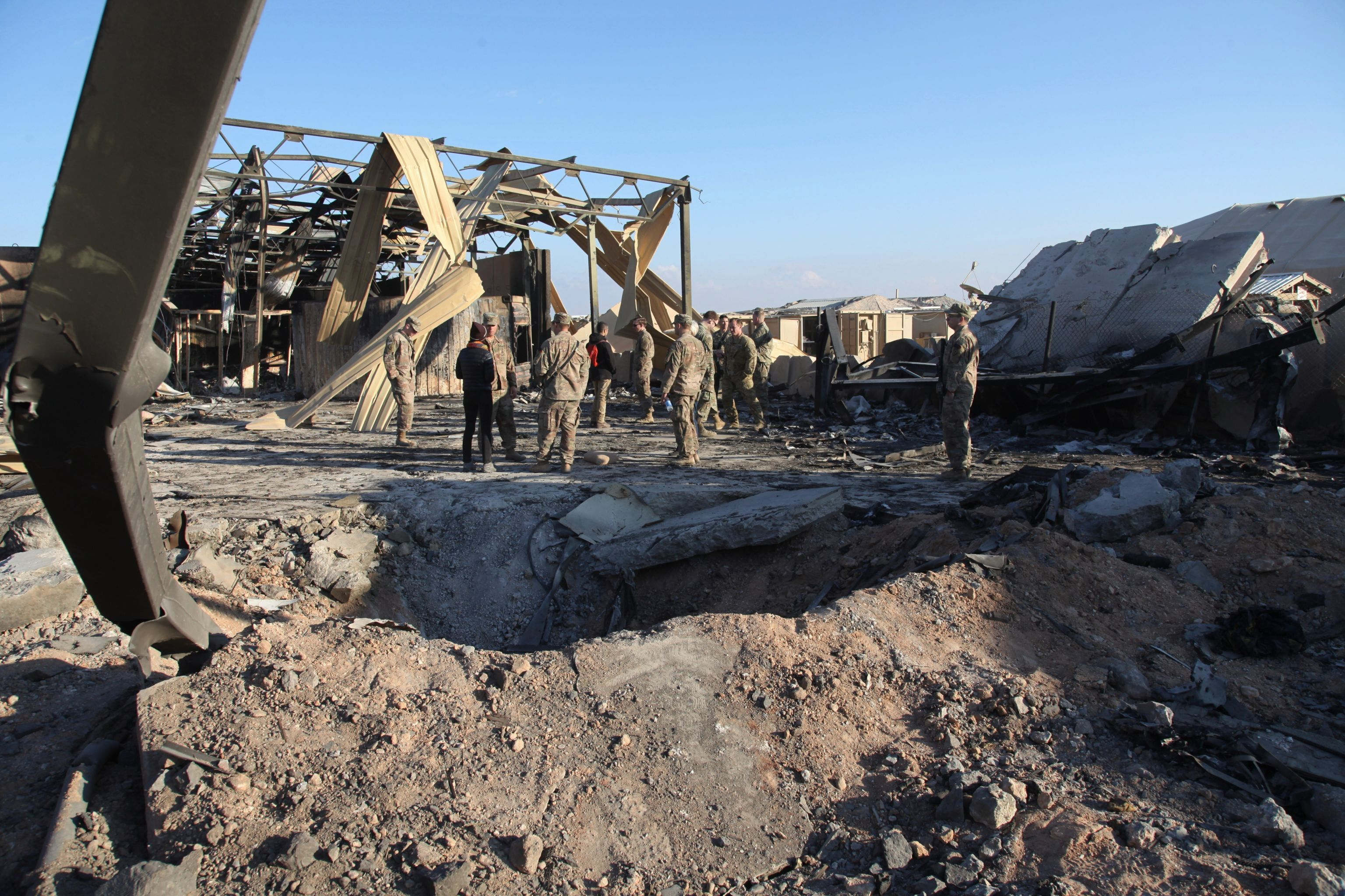 In this Monday, Jan. 13, 2020 photo, U.S. Soldiers stand at spot hit by Iranian bombing at Ain al-Asad air base, in Anbar, Iraq