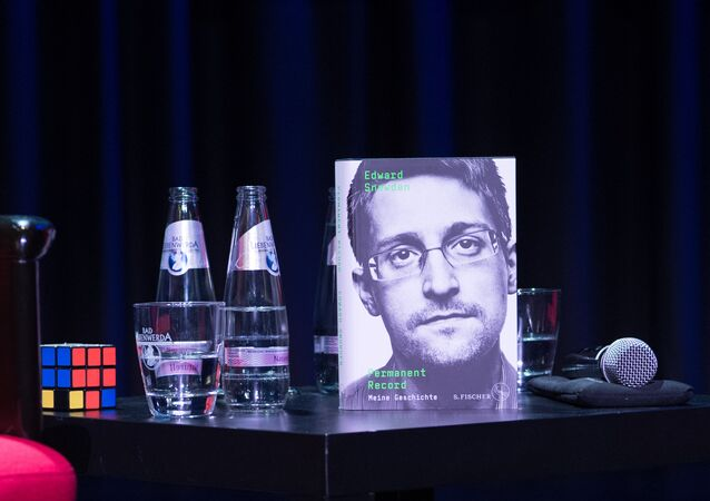 A copy of the book titled Permanent Record by US former CIA employee and whistleblower Edward Snowden is seen next to a Rubik's cube during a video conference on September 17, 2019 in Berlin. - In his book, Snowden tells among others that he used a Rubik's cube to smuggle secret data out of the rooms of the US intelligence service National Security Agency (NSA)